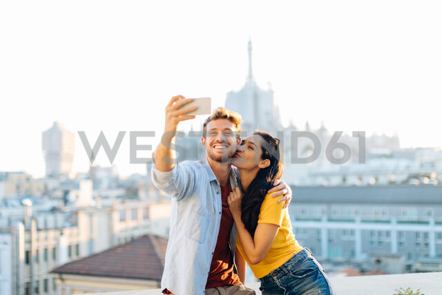 Couple taking selfie on edge of rooftop terrace, Milan, Italy - CUF47626 - Sofie Delauw/Westend61