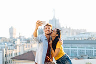 Couple taking selfie on edge of rooftop terrace, Milan, Italy - CUF47626