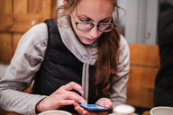 Young woman using smartphone in cafe - CUF47632