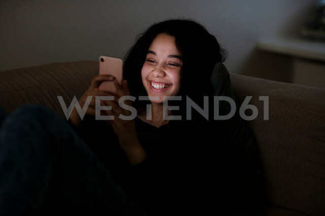 Teenage girl lying on sofa in dark reading text message - CUF47671 - T2 Images/Westend61