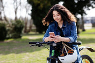 Teenage girl texting on pushbike - CUF47680