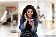 Teenage girl reading text message on cellphone in school - CUF47683
