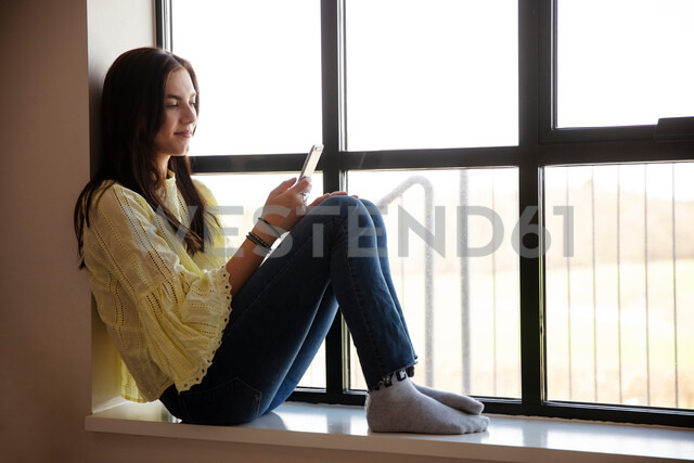 Teenage girl reading text message on cellphone by glass window - CUF47686