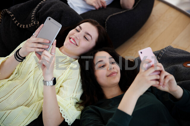 School friends lying on beanbags and texting at school - CUF47692
