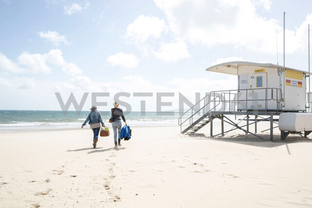 Sisters leaving after picnic on beach - CUF47710