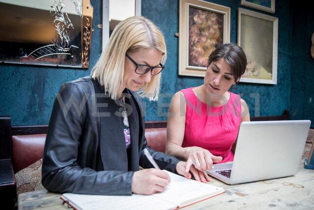 Women brainstorming business ideas in restaurant - CUF47719