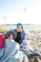 Mother and toddler girl in blanket on beach - CUF47743