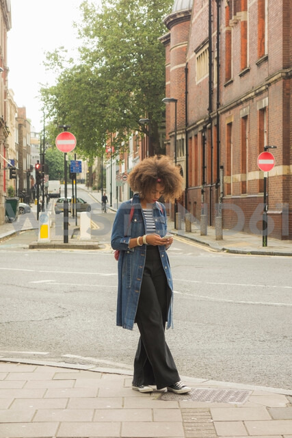Woman checking cellphone on pavement, London, UK - CUF47761
