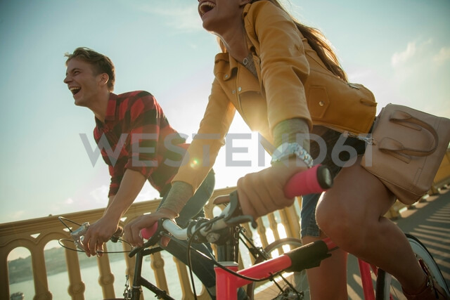 Couple crossing bridge on bicycles, Budapest, Hungary - CUF47782