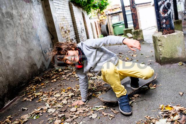 Boy falling off skateboard on street - CUF47818