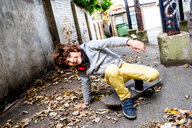 Boy falling off skateboard on street - CUF47818