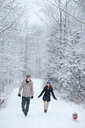 Young couple walking dog in snow covered forest, Ontario, Canada - CUF47824