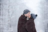 Romantic young couple kissing in snowy forest, Ontario, Canada - CUF47827