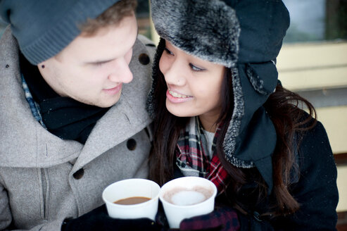 Young couple in winter hats having takeaway drinks - CUF47830