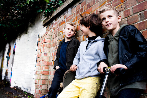 Boys leaning against brickwall - CUF47842