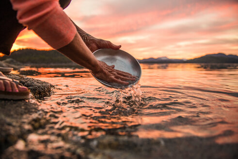 Mature woman washing plate at sunset, cropped, Quadra Island, Campbell River, Canada - CUF47863