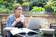 Pregnant mid adult woman looking at laptop on patio table - CUF47875