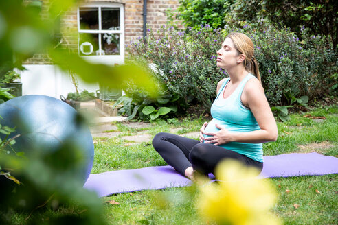 Pregnant mid adult woman practicing yoga meditation in garden - CUF47878