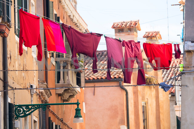 Red and pink clothing on clothesline outside traditional houses, Venice, Veneto, Italy - CUF47887