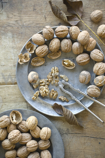 Whole and cracked organic walnuts and nutcracker on tin plates - ASF06265