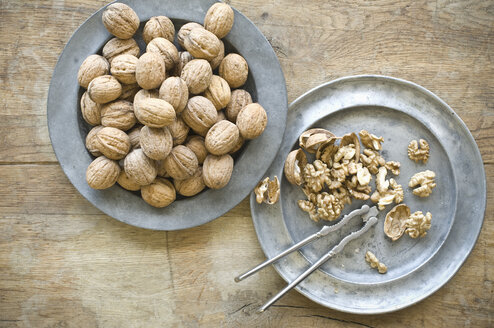 Whole and cracked organic walnuts and nutcracker on tin plates - ASF06268
