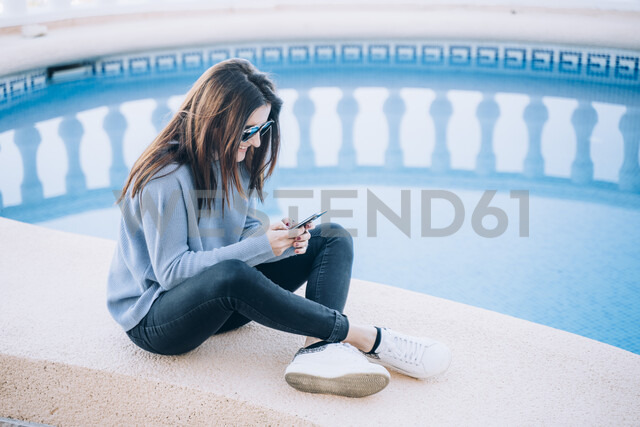 Woman using smartphone at swimming pool - OCMF00216