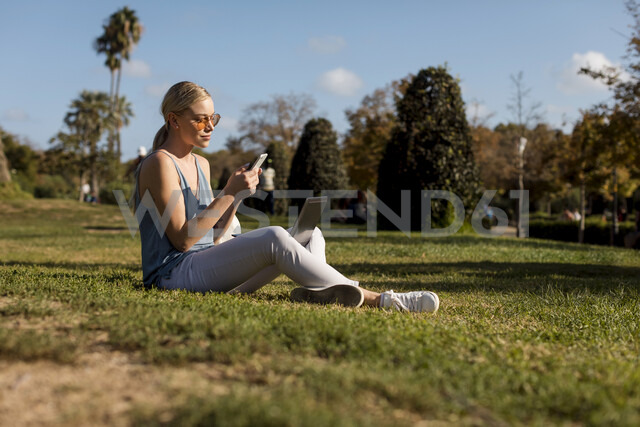 Young woman sitting in park using cell phone and laptop - MAUF02298