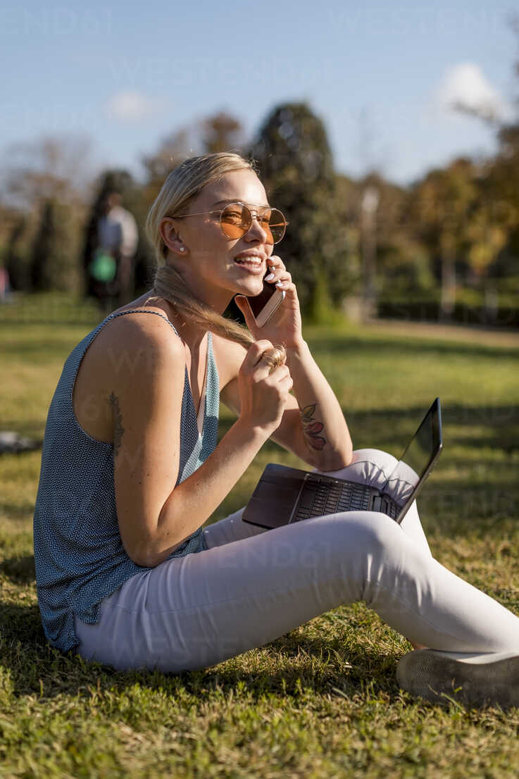 Young woman sitting in park using cell phone and laptop - MAUF02301 - Mauro Grigollo/Westend61