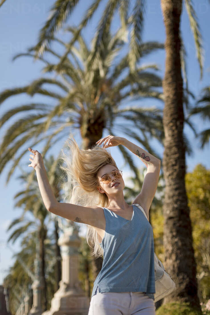 Carefree young woman moving under palm tree - MAUF02304 - Mauro Grigollo/Westend61