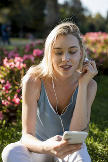 Smiling young woman sitting in park with cell phone and earbuds - MAUF02307