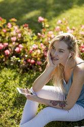 Smiling young woman sitting in park with cell phone and earbuds - MAUF02310