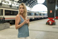 Young woman with cell phone at the train station looking around - MAUF02313