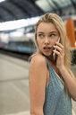 Portrait of young woman on cell phone at the train station looking around - MAUF02316