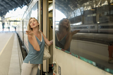 Young woman entering a train at the train station blowing a kiss - MAUF02319