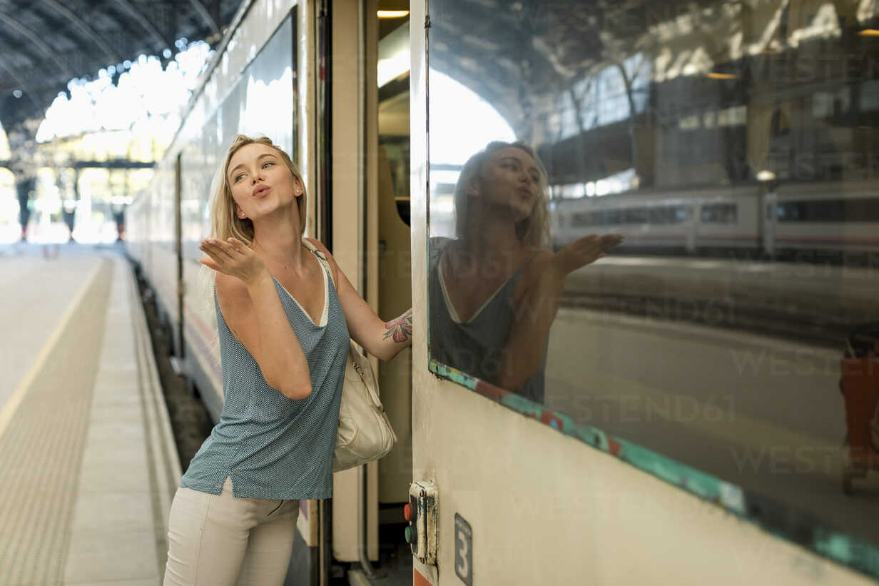 Young woman entering a train at the train station blowing a kiss - MAUF02319 - Mauro Grigollo/Westend61