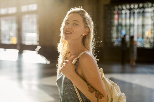 Portrait of smiling young woman with a tattoo in backlight - MAUF02322
