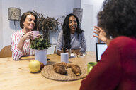 Three women with laptop talking at table - GIOF05477