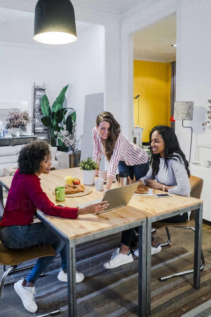 Three happy women with laptop at table - GIOF05480 - Giorgio Fochesato/Westend61