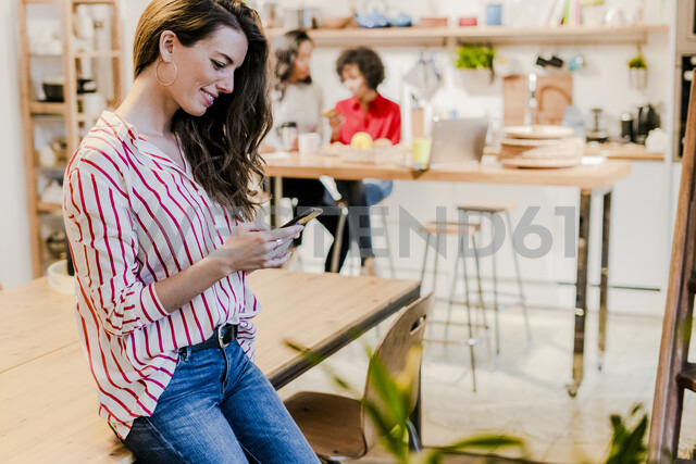 Smiling woman with cell phone at table - GIOF05489