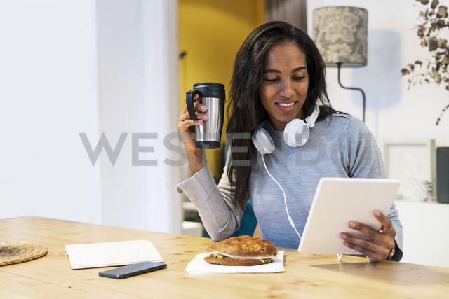 Smiling woman using tablet at table - GIOF05501