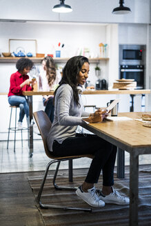 Smiling woman using tablet at table - GIOF05504