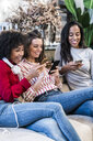 Three smiling women sitting on couch using cell phones - GIOF05507