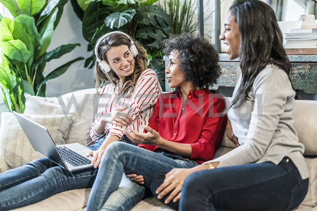 Three happy women with laptop sitting on couch - GIOF05510