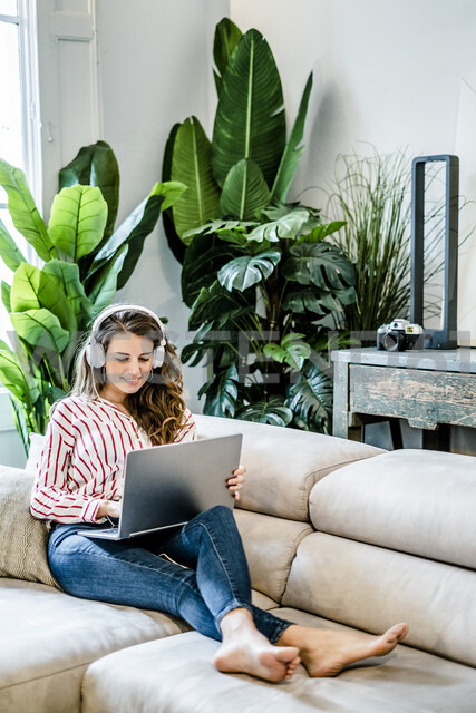 Smiling woman with laptop and headphones sitting on couch - GIOF05513