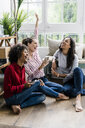 Three carefree women sitting on the floor at home with cell phones - GIOF05528