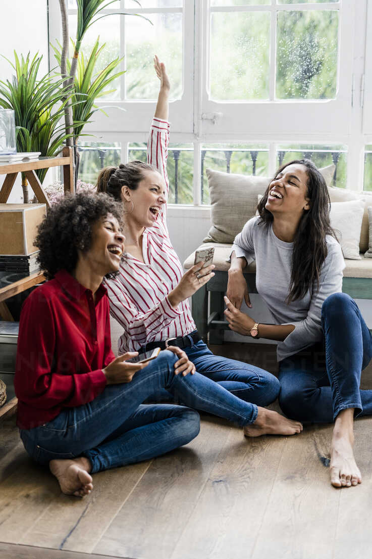Three carefree women sitting on the floor at home with cell phones - GIOF05528 - Giorgio Fochesato/Westend61