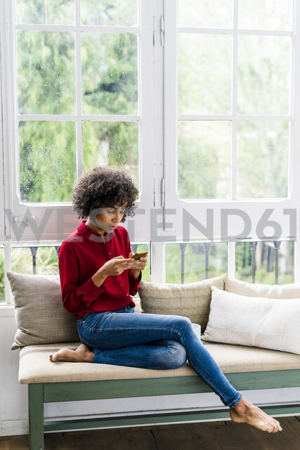 Serious woman sitting at the window at home using cell phone - GIOF05534