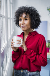 Smiling woman with cup of coffee looking out of window at home - GIOF05537