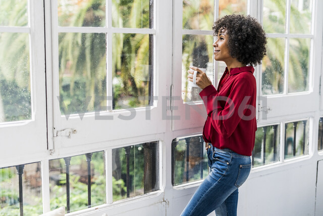 Smiling woman with cup of coffee looking out of window at home - GIOF05540 - Giorgio Fochesato/Westend61