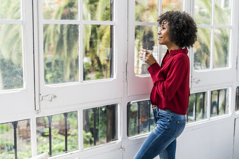 Smiling woman with cup of coffee looking out of window at home - GIOF05540